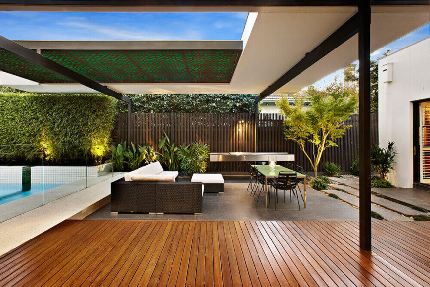 Here we see the carefully balanced interplay of elements, as white house structure meets black metal support beams above the rich hardwood and granite flooring. The sleek fence is supplemented by greenery.