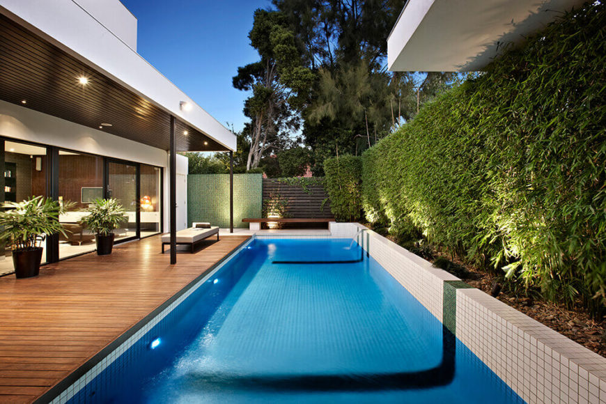 The large fence and bamboo growth creates a supremely private space in this outdoor area, with the pool at center. Unique water features run out from beneath the bamboo, filling the pool.