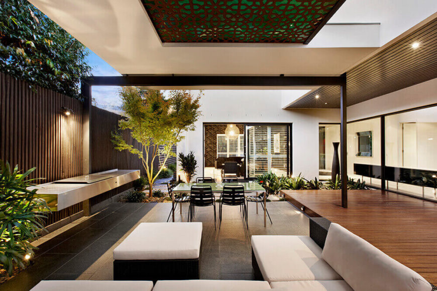 Seen from the opposite side, we can take in the fluid floor plan, expanding from indoors and layering over various materials in different segments of the patio space.