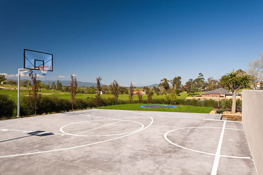 Here's a look at the basketball court, nicely sequestered from the rest of the landscape by a small feature wall. In the distance, we can see the built-in trampoline.