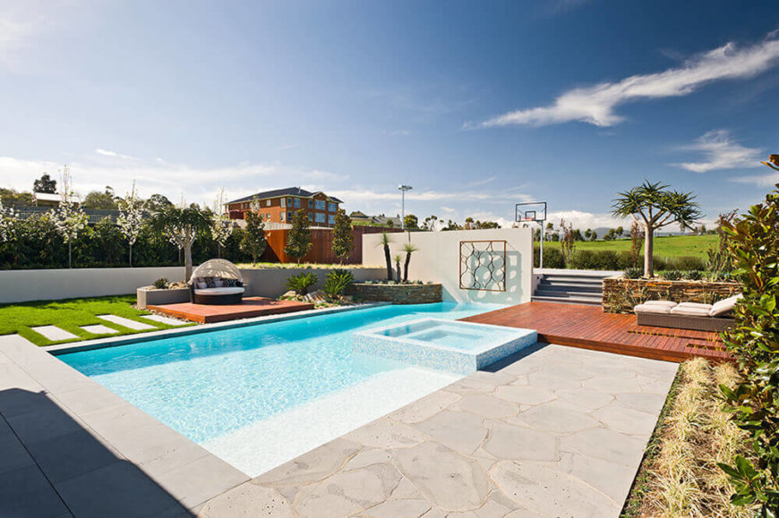 The pool is an exquisite construction, wrapping a built-in jacuzzi and flanked by a pair of raised natural wood platforms. The wall at the far end obscures the basketball court.