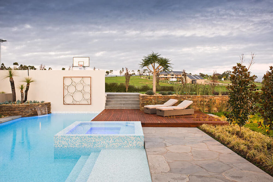 The pool is wrapped in micro tile for an intricate, textured look that helps set it apart from the surroundings. The surrounding patio elements add contrast and a timeless richness.