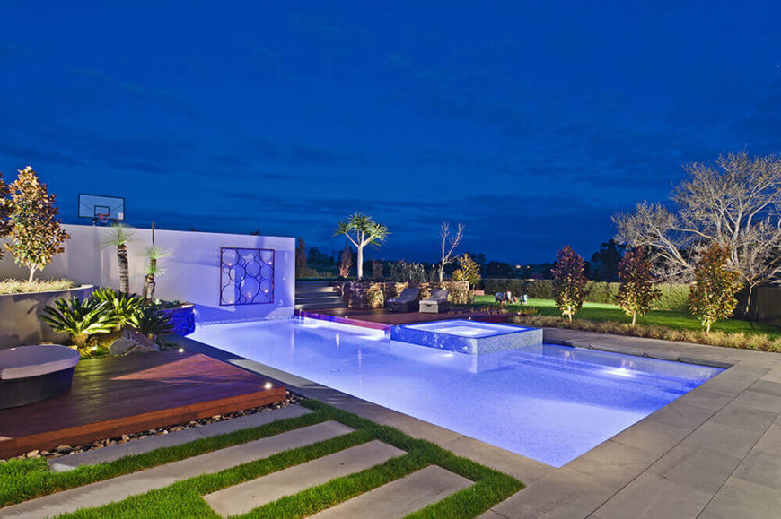 At night, an intricately patterned set of subtle lighting elements brings the entire space to new life. The glow of the pool extends over the patio.