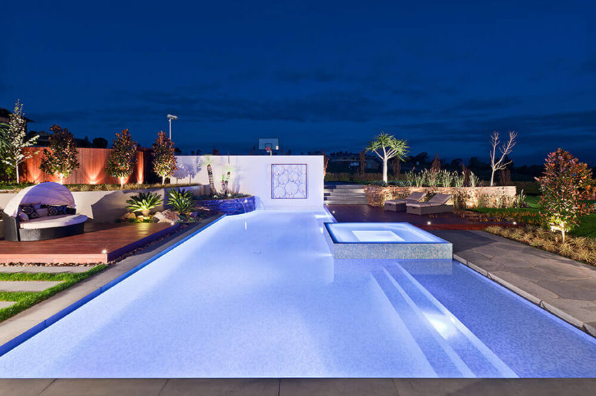 The lighting scheme helps highlight the carefully crafted design of the entire landscape, from trees and plants to the rich natural wood walls and platforms. The pool becomes even more of a centerpiece at night.