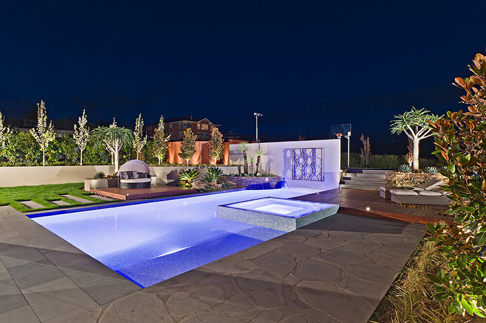 This custom swimming pool features an underwater lighting for additional style.