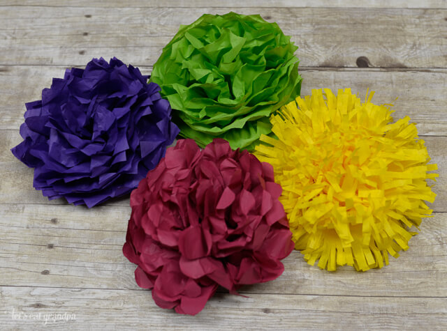 These colorful and fluffy paper pom-poms are made to resemble flowers including chrysanthemums, and look great hanging from the ceiling. Perfect for teen or dorm decor!
