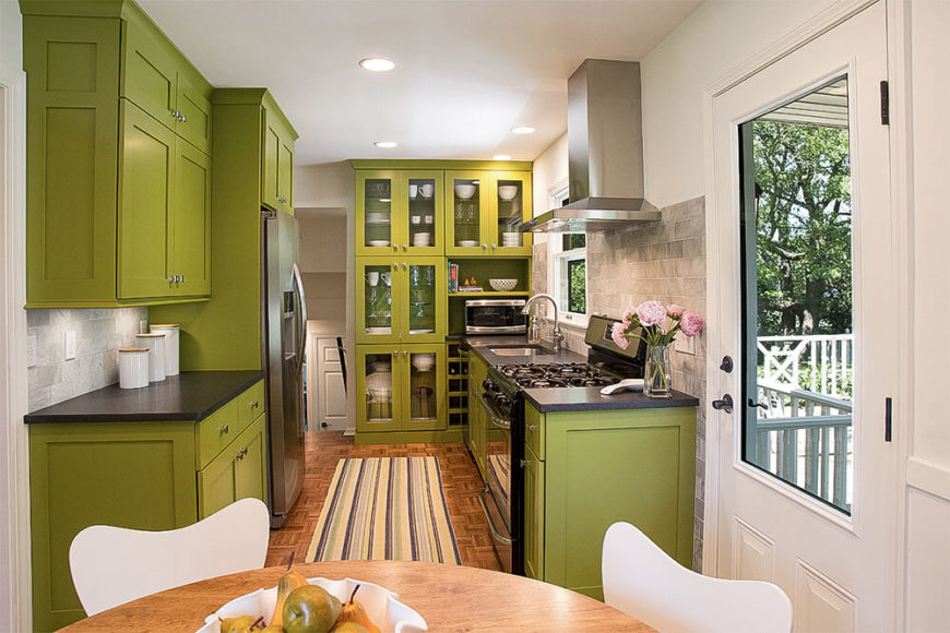 The kitchen stands out with bold green cabinetry from floor to ceiling, featuring sleek surfaces and a handful of glass door cupboards. A grey tile backsplash and stainless steel appliances complete the modern look.
