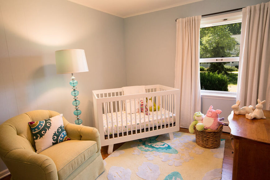 This cozy nursery room features a single button tufted armchair and contemporary white crib, along with a traditional natural wood dresser over hardwood flooring.