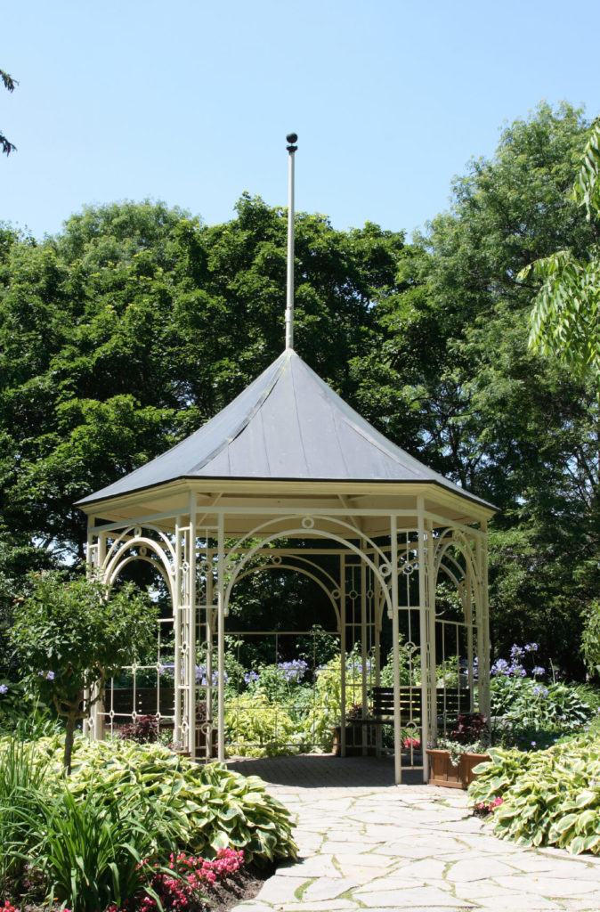This shady gazebo is perfect for sitting under and relaxing near your garden. The detailed sides and arches are a perfect fit for a garden area. This style of gazebo would also look great accompanied by vines or other climbing plants.