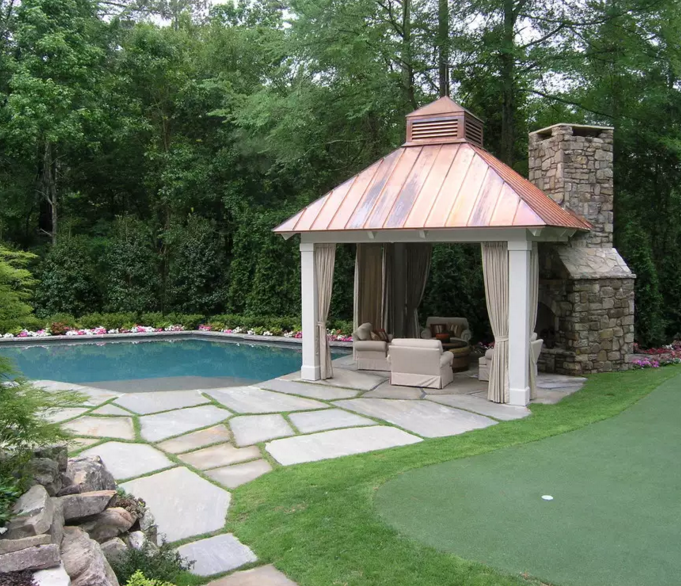 This gazebo has an attached fireplace, making this gazebo a fantastic place to relax under late into the night. These elements create a useful and alluring poolside space to socialize and hang out in.