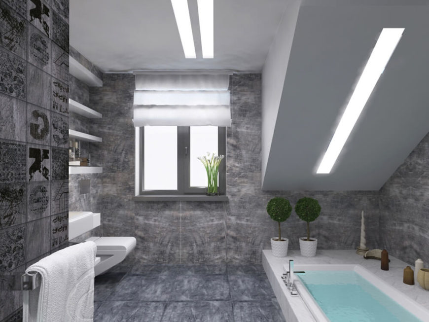 The primary bath is awash in rich grey tile from floor to ceiling, with unique builtin shelving and a large sunken soaking tub.