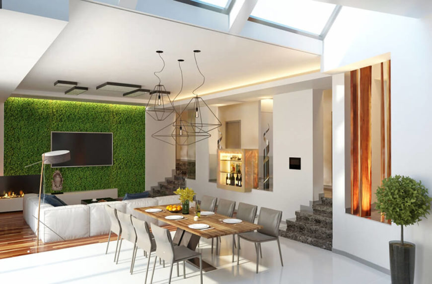 Looking toward the living room area, we see a flat panel TV mounted on the full height living wall, surrounded by greenery and lit from above. This startling element gives the modern space a more textured, timeless appeal.