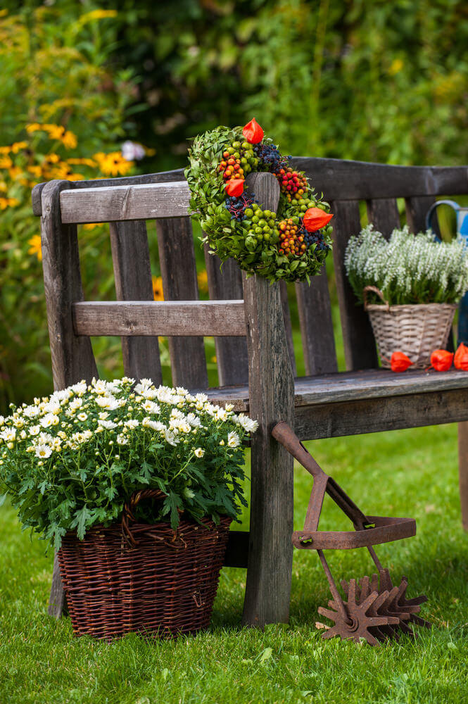 This old and rustic wooden garden bench looks more decorative with added flower blossoms stacked in the woven basket.