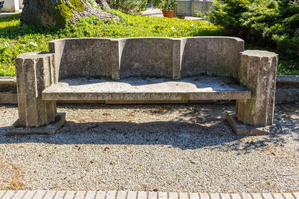 A concrete bench designed with a curvy back rest and supports.