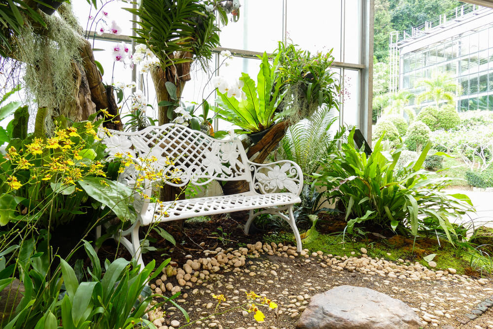 Hidden in the greenery is a white metal garden bench with decorative floral moldings.