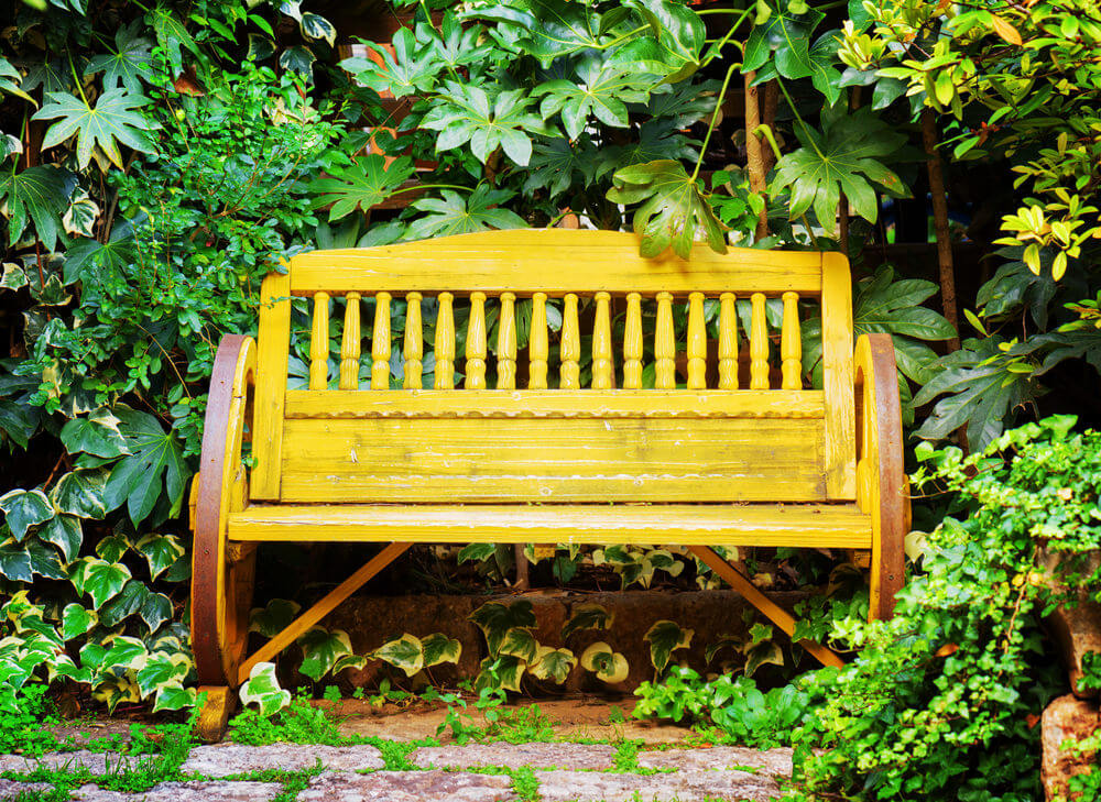 Bright yellow paint gives this wagon wheel garden bench a nice contrast with the green shrubs around it.