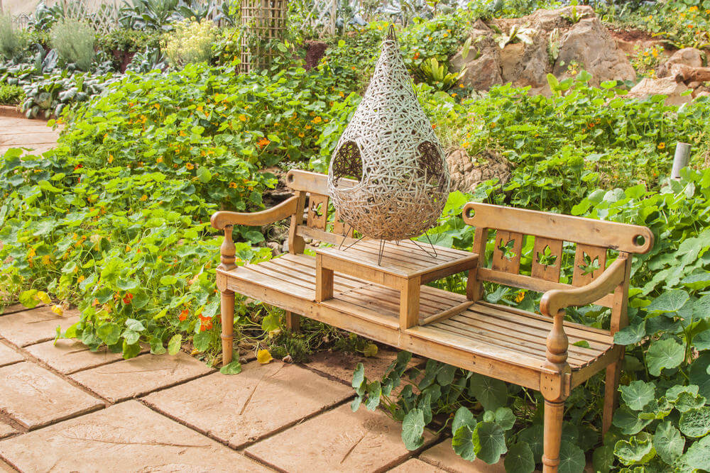 This is a creative, decorative and functional garden bench made of wood with a built-in tea table at its center.