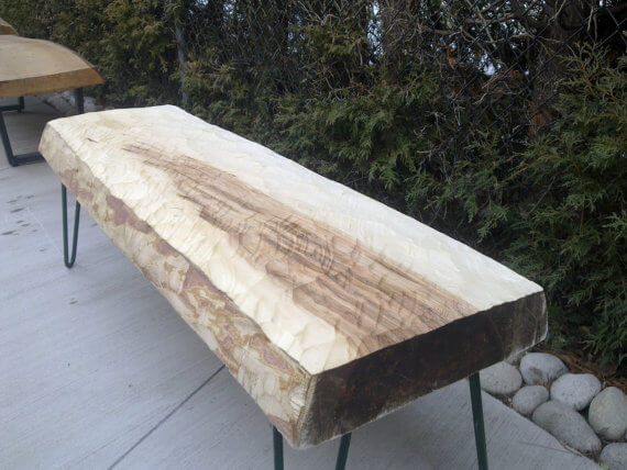 This one is a hand hewn bench made from a single piece of a maple tree and metal bottom supports.