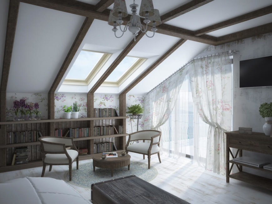 A major draw of this bedroom is the sloped ceiling, skylights, and broad, irregularly shaped glass balcony doors. This allows for an abundance of sunlight in the high contrast room. At left, a unique dark wood bookshelf is built into the wall.
