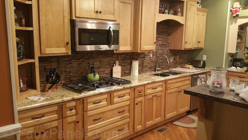 A dark layered stone backsplash adds texture and contemporary style to this light wood and granite kitchen layout. The stone goes up in panels, meaning it's simpler to apply than the standard tilework usually found on kitchen backsplashes.
