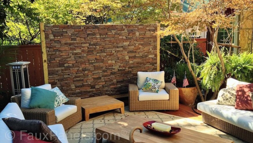 This patio's privacy wall is covered in faux stone paneling, adding visual interest to the patio's seating area, while also extending another foot or so above the wooden privacy fence.