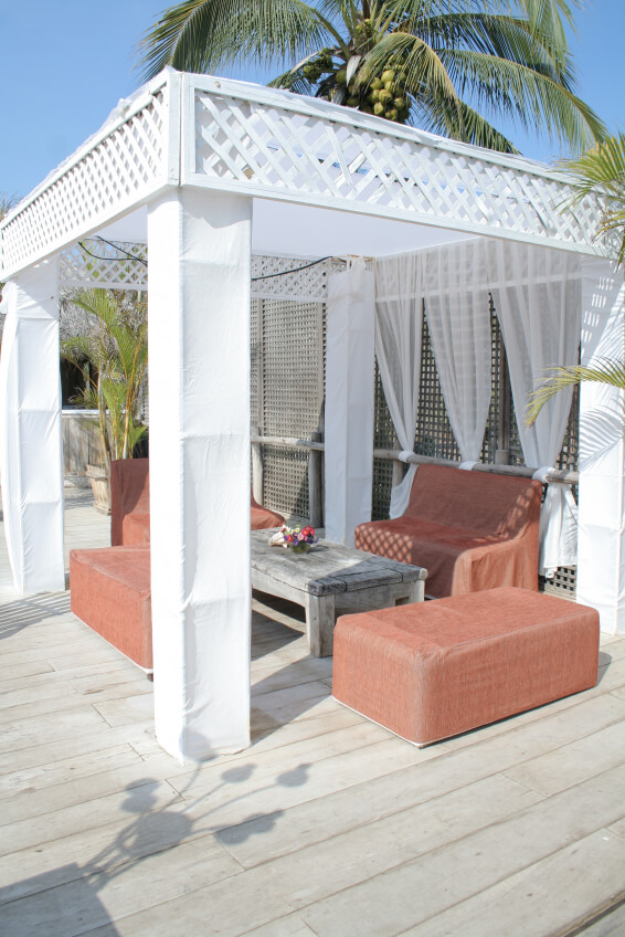 Here is a white breezy gazebo that sets the stage for a welcoming and homey outdoor space for you and your friends to gather. You can relax and take it easy in this uncomplicated space with rustic furniture.