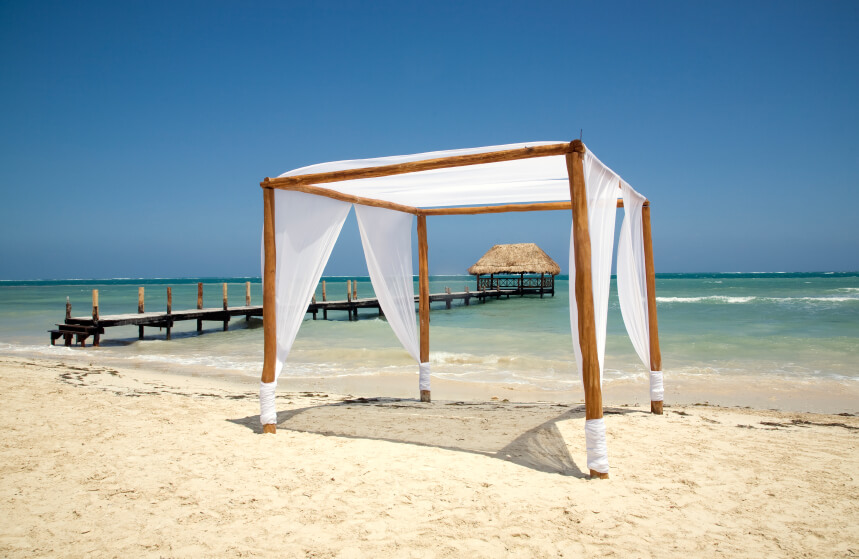 This gazebo is made from a basic wood frame and has light cloth around the pillars as well as the ceiling. This creates a breezy and light design that is very inviting.