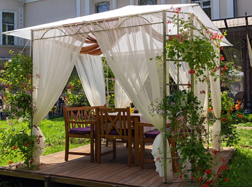 White curtains and hanging flowers adorn this simple metal frame gazebo. When a gazebo has a simple structure like this you can decorate it anyway you want and fit it into any style you like.