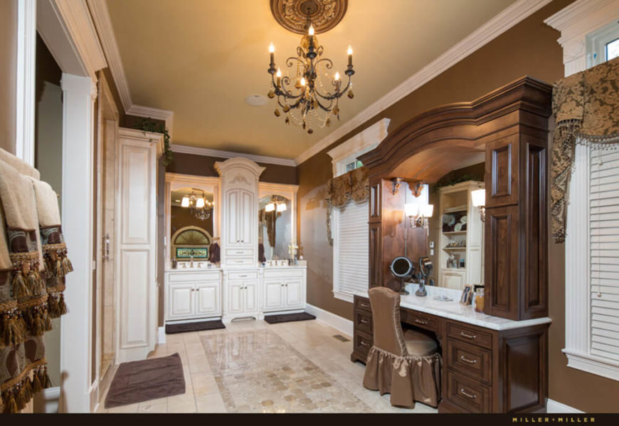 Similarly, the primary bath is awash in rich materials, from ornate wood and marble vanity to the marble flooring. A chandelier hangs in this room, illuminating every curve and fold of the molding and window frames.