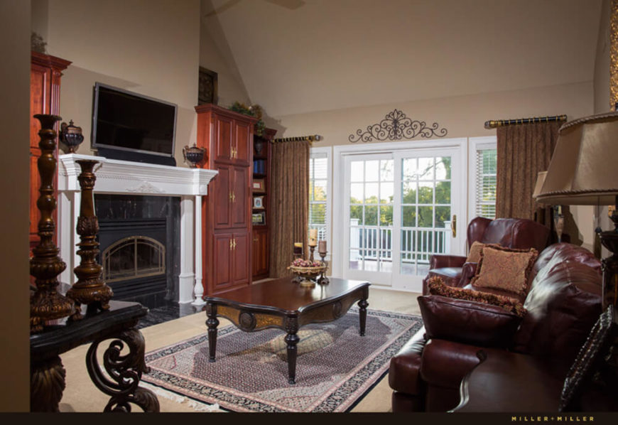 In this relatively cozy, compact family room, we see another large dominant fireplace along with a set of rich leather furniture. Sliding glass doors lead directly to the upper level patio.