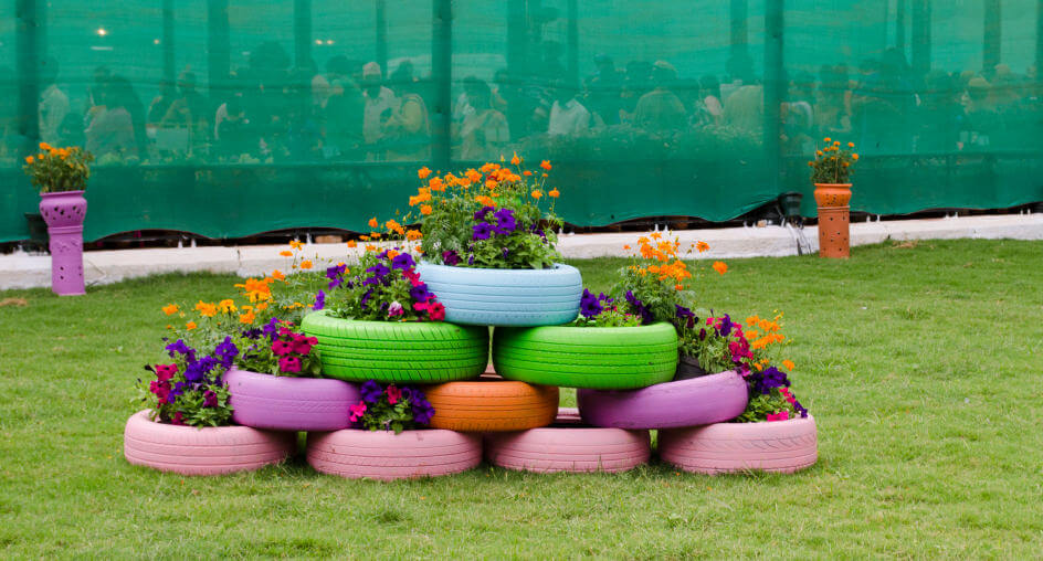 Another pyramid tire planter garden with pink, orange, green and light blue tires.