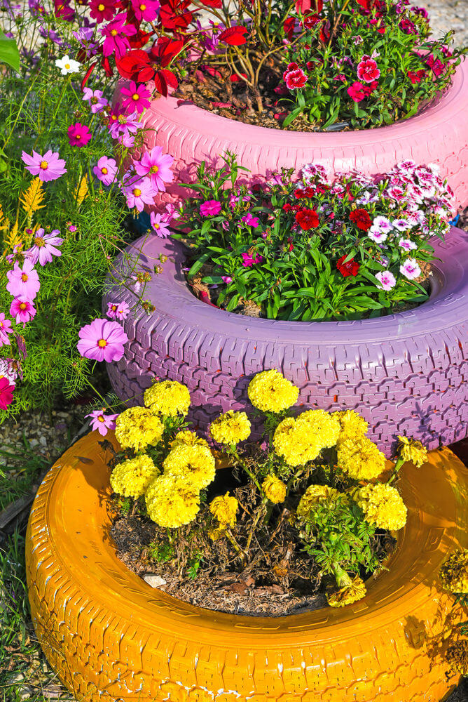 Close up of a pretty tire planter garden with nicely painted tires holding a beautiful array of flowers.
