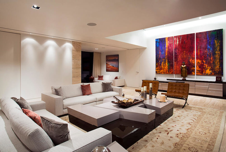 Recessed lighting brightens up darker areas without cluttering the open space with additional lighting fixtures. The paintings add splashes of bold colors that liven up the design with motion, breaking up the simple lines and simple palette.