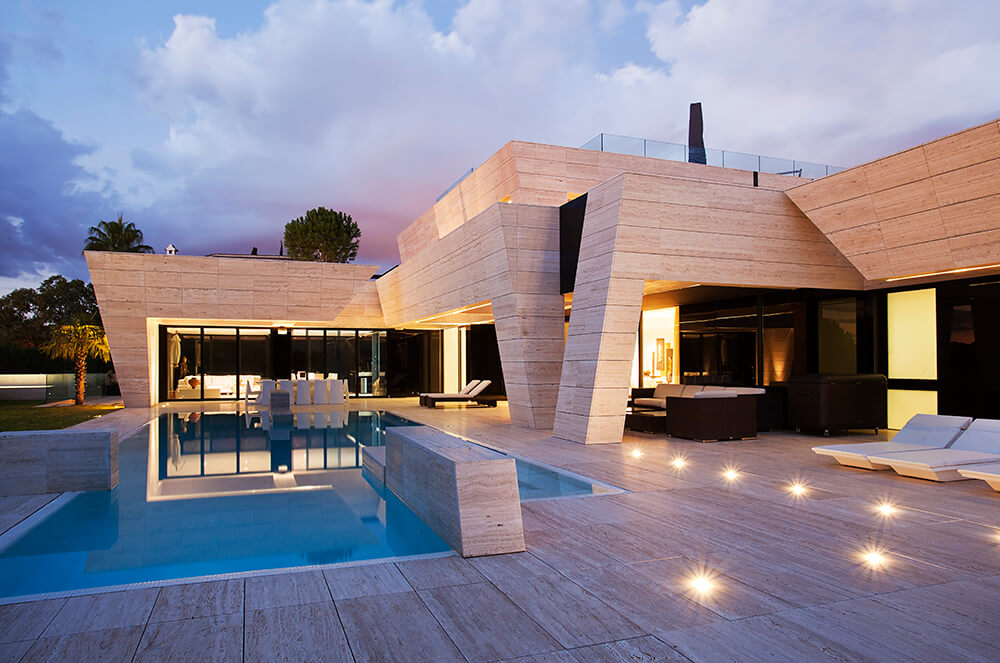 Stylish and modern home featuring a custom infinity pool surrounded by the home's deck.