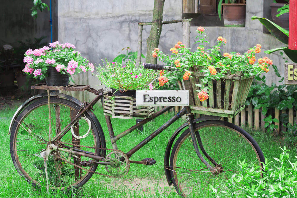 Bicycle flower planter also serving as a sign.