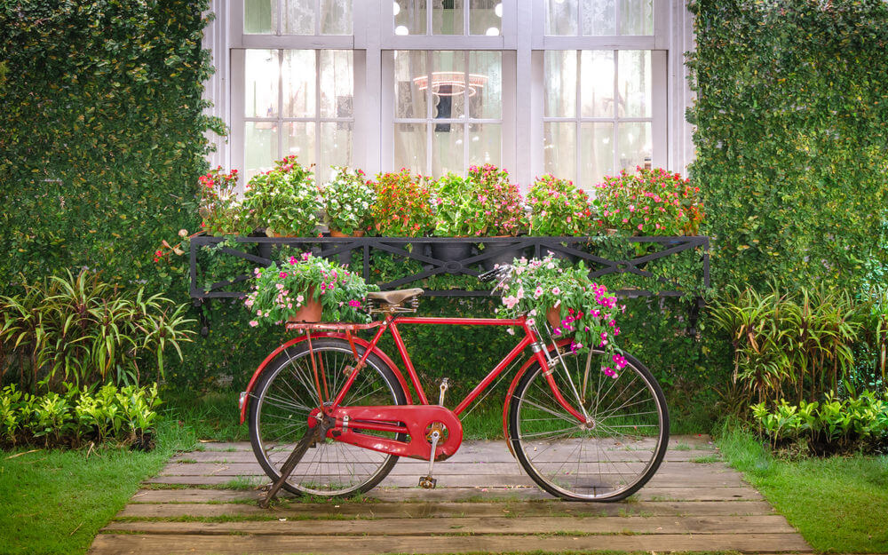 Bright red bicycle with large flower pots on the front and rear in a beautiful garden setting.