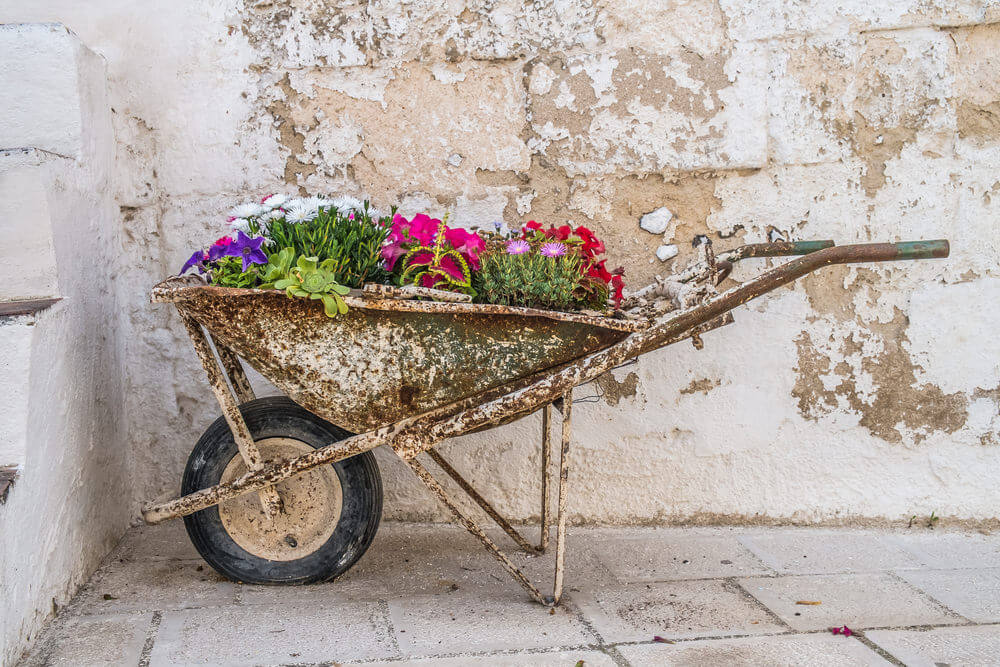 It's contemporary metal wheelbarrow that looks like it was hammered with a sandblaster.
