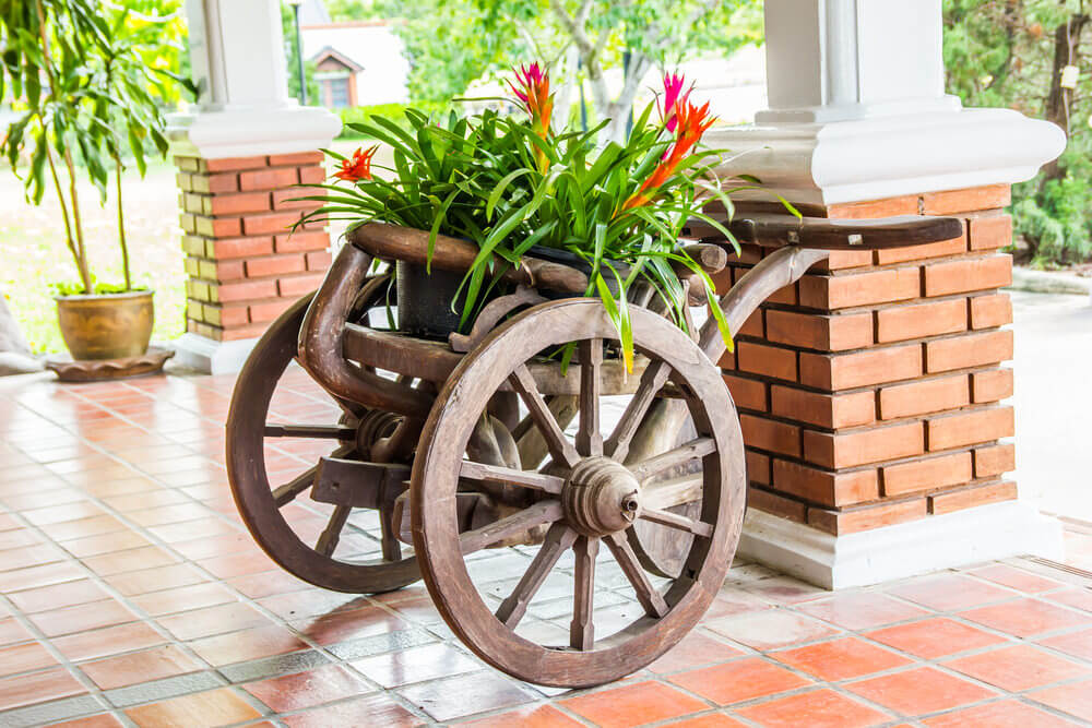 Stunning 2-wheeled wheelbarrow planter with large wooden wheels.