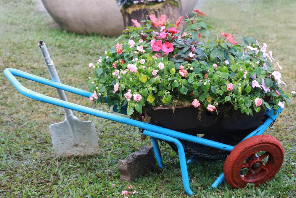 Metal framed cart designed to hold a large flower pot.
