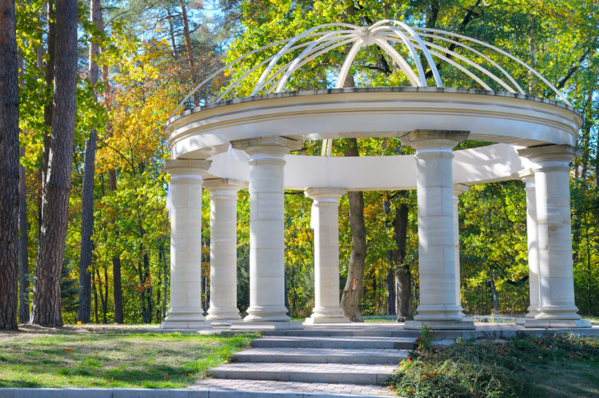 This decorative gazebo has a minimal roof and large pillars. It does not hold a solid roof like many gazebos, but rather sets the stage for an interesting gathering area.