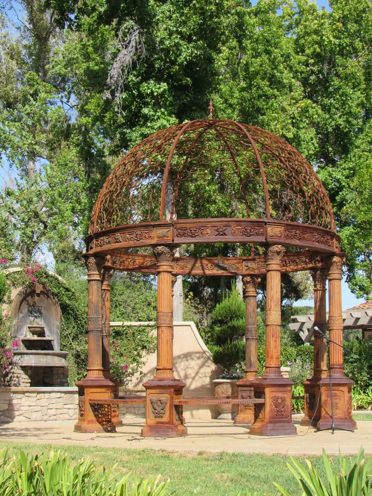 This rustic and weathered gazebo is a design feature that is interesting and draws a lot of attention. The patina and aging of the piece make it stand out and build a mystique.