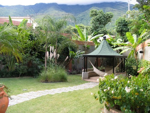 This relaxing and shady gazebo sits at the end of a stone path. A hammock hangs in the gazebo so that you can swing comfortably in the shade.
