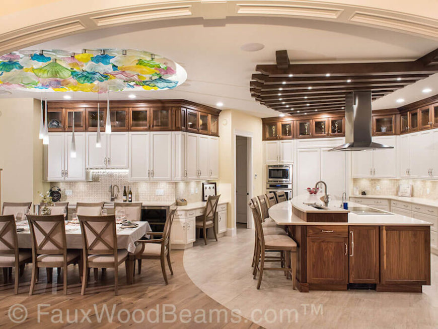 This beautiful kitchen features plenty of natural wood against white cabinetry and countertops. Faux wooden beams are attached to the ceiling, fanning out over the spacious kitchen island.