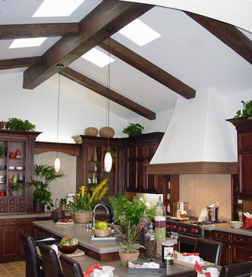 The rich dark stain of the faux wooden beams in this kitchen are a perfect match for the cabinetry. The beams cross-section the kitchen's vaulted ceiling, with a skylight in between each pair.