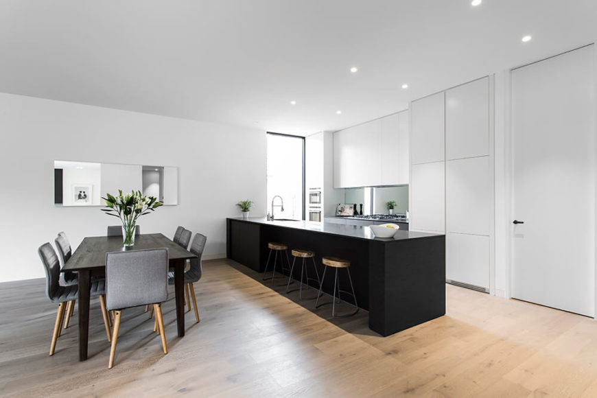 The dining and kitchen areas are defined by the high contrast between white walls and dark elements. The large island includes a built-in sink, plenty of countertop space, and an area for dining on bar stools.