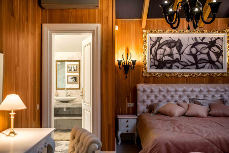 The second bedroom sports a warmer palette, with rich wood wall paneling and lighter furniture. Her we see the cozy layout with private bathroom access.