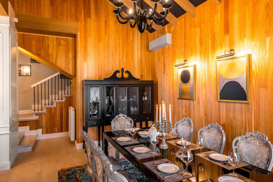 The dining room boasts a mixture of sleek lines and ornate furniture, with a monolithic black table at center, flanked by Victorian styled dining chairs. A black China hutch adds to the high contrast look.