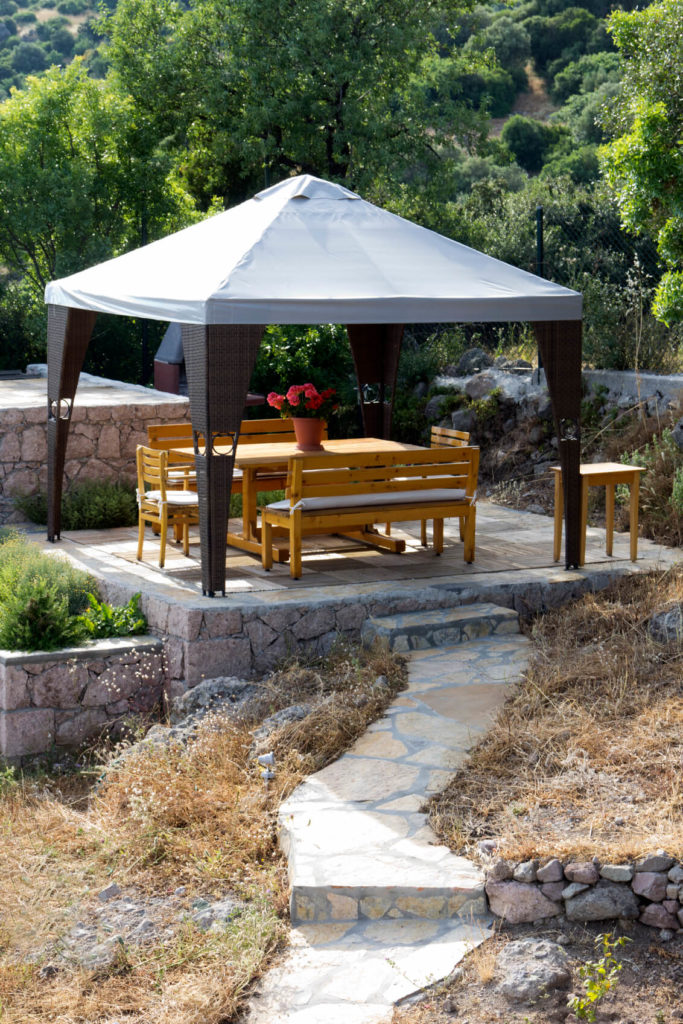 This gazebo is perfect on a patio. It sits tall above a picnic table, providing an inviting place to gather and share a meal. This patio will have your guests hanging out in your yard for sure.
