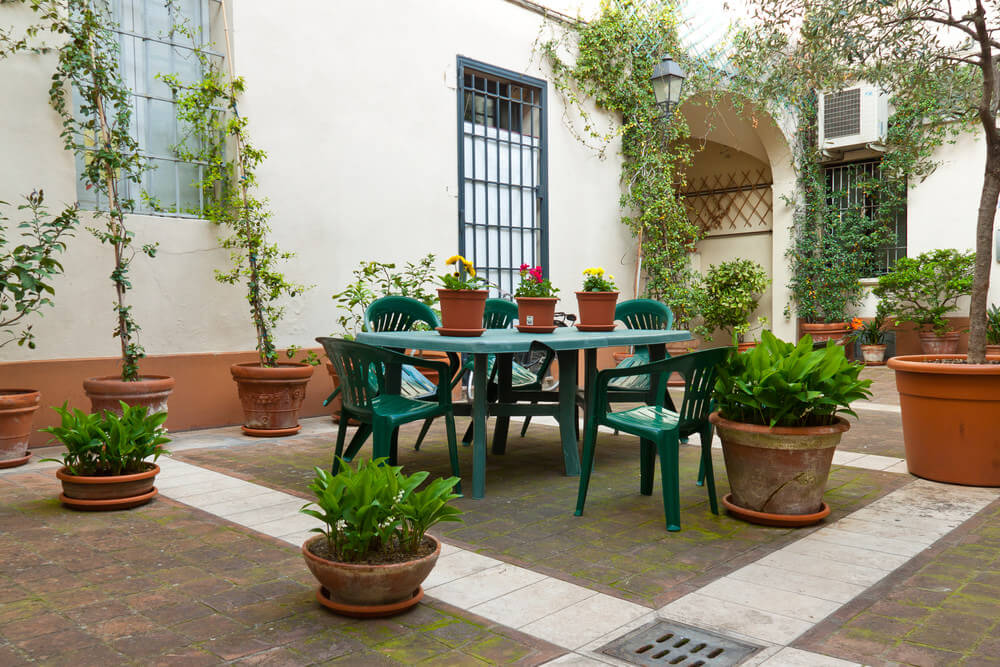 Scatter patio flower pot effect here with large potted flowers and plants placed throughout a large patio space.