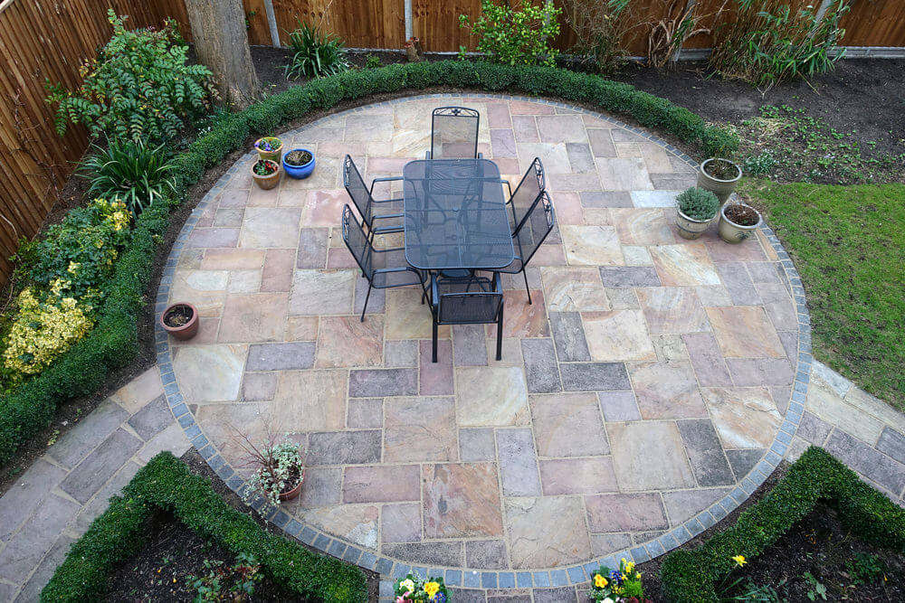 Overhead view of round patio with potted plants, trees and flowers on the outside of the circle.